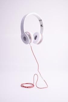 Coup vertical d'un casque blanc avec un câble rouge