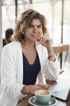 Coup vertical confiant réussie blonde aux cheveux bouclés jeune femme entrepreneur pigiste responsable des médias sociaux travaille à l'extérieur du concept d'économie de bureau gig, boire un café café assis près d'un ordinateur portable.