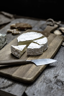 Coup vertical de délicieux fromage brie sur une terrasse en bois