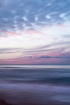 Coup vertical du beau ciel coloré sur la mer pendant le lever du soleil