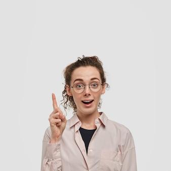 Coup vertical d'une femme à l'air agréable avec une peau tachetée de rousseur et des cheveux bouclés, pointe avec son index vers le haut, porte des lunettes, attire votre attention, porte une chemise, isolée sur un mur blanc
