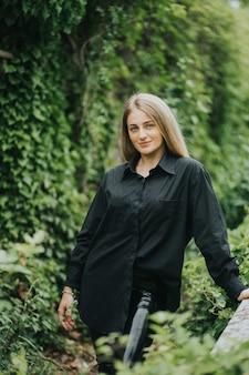 Coup vertical d'une femme blonde caucasienne à la mode posant entouré de verdure