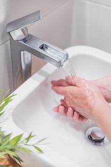 Coup vertical de femme se laver les mains avec du savon et de l'eau