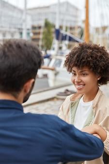 Coup vertical d'une jeune fille souriante à la peau sombre a une coupe de cheveux afro, un sourire à pleines dents