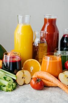 Coup vertical de jus de fruits et de légumes frais dans des bouteilles en verre, différents ingrédients, fond blanc.
