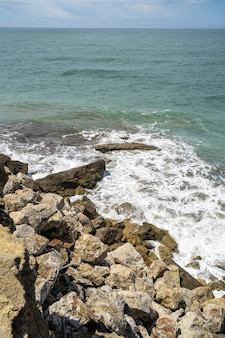 Coup vertical de la mer entourée de rochers sous la lumière du soleil pendant la journée