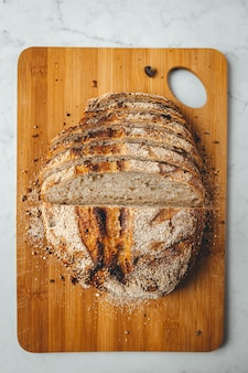 Coup vertical de pain au levain frais sur planche à découper en bois