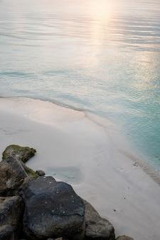 Coup vertical d'une plage de sable avec le reflet du soleil dans l'eau bleue