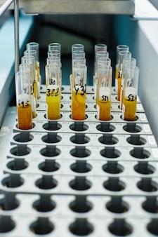 Coup vertical de tubes à essai avec des réactifs médicaux jaunes avec des marques noires sur elle