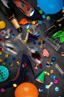 Coup de vue de dessus après une fête avec des bouteilles vides, un verre de vin, des chaussures de fille et des accessoires de fête