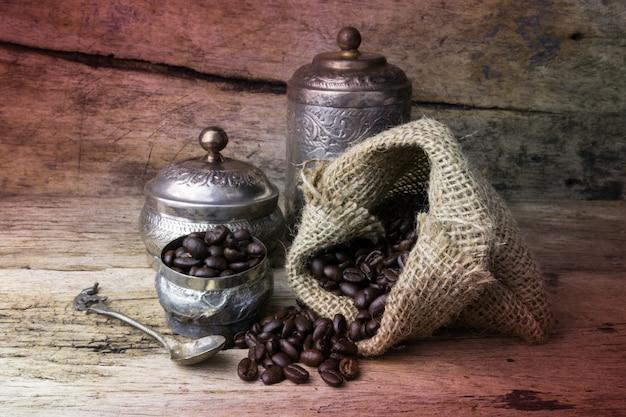 Coupe en argent et grains de café dans un sac en toile de sac sur fond en bois