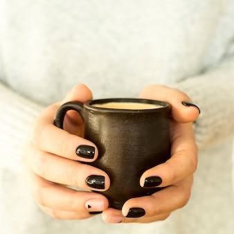Coupe d'argile avec du café dans les mains d'une fille avec une manucure noire minimaliste