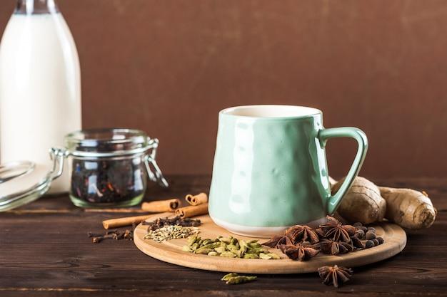 Coupe d'argile sur une planche de bois sur un fond sombre. une tasse de thé masala. épices clous de girofle, fenouil, cannelle, cardamome, lait.