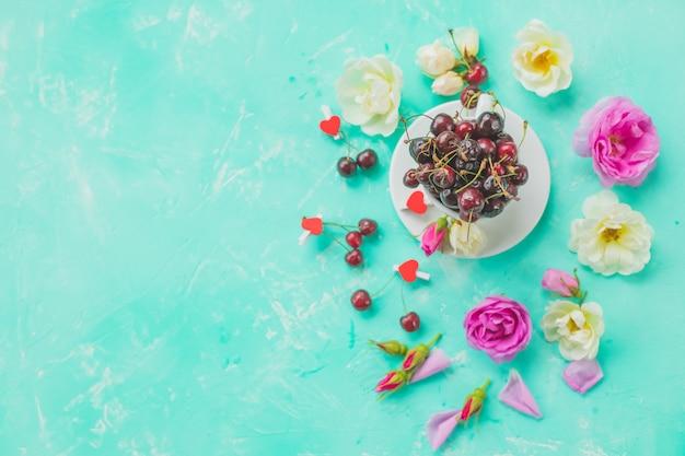 Coupe de baies de cerise, thé à la rose avec une branche de bouquet de roses