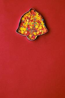 Coupe-biscuits en pain d'épice en forme de cloche de noël rempli de pépites de sucre colorées sur fond rouge. espace de copie. carte de noël
