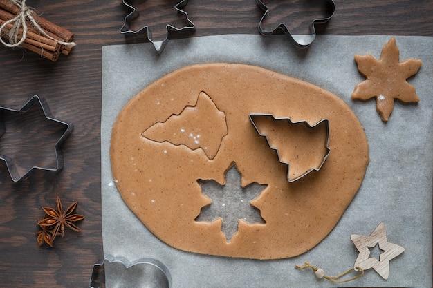 Coupe de biscuits de pain d'épice à partir de pâte pâtissière épicée salée sur table en bois avec couteaux