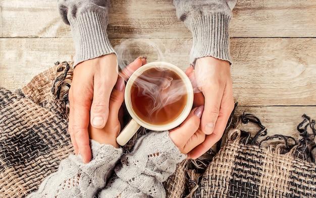 Coupe boisson pour le petit déjeuner entre les mains des amoureux. mise au point sélective.