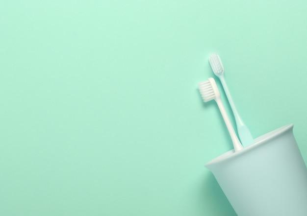Coupe avec des brosses à dents menthe et blanc sur le mur de menthe.
