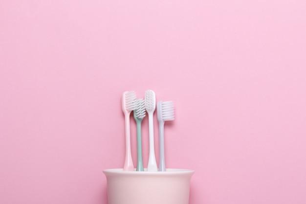 Coupe avec brosses à dents roses, vertes, grises et blanches sur mur rose.