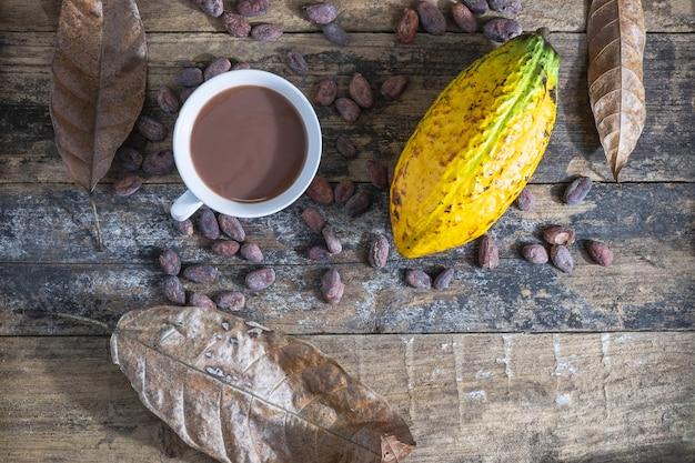 Coupe de cacao et fruits de cacao sur une table en bois