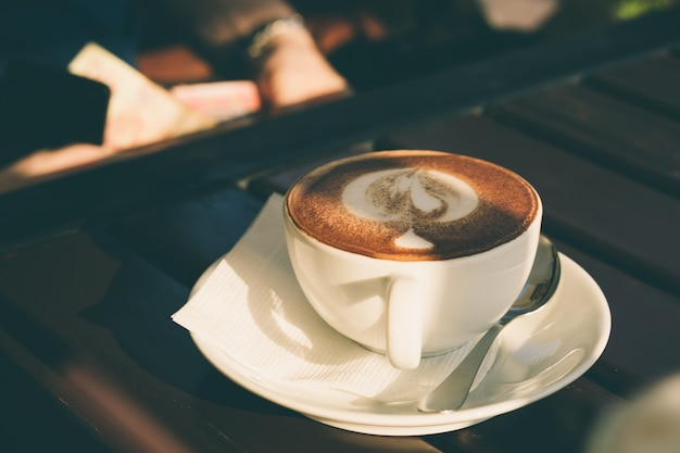 Coupe de cappuccino à la cannelle sur une table en bois dans un café