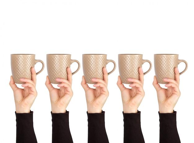 Coupe en céramique brune dans une main féminine sur blanc