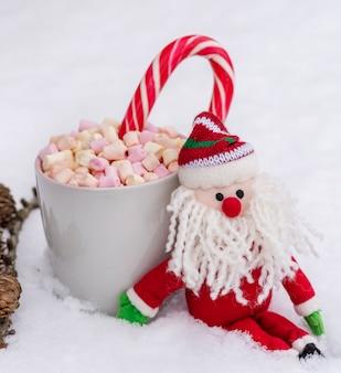 Coupe en céramique grise avec chocolat chaud, guimauve et bonbons