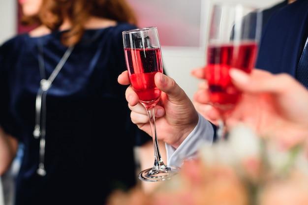 Coupe de champagne rouge dans la main d'un homme en costume au festival