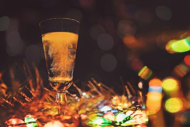 Une coupe de champagne sur la table sur les décorations de noël. la célébration de noël.