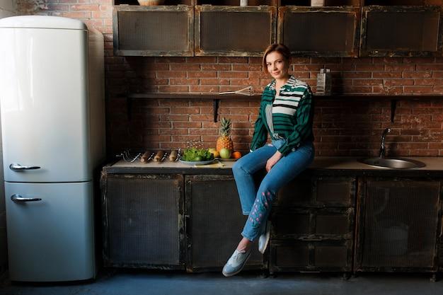 Coupe de cheveux courte belle jeune femme assise sur la table de la cuisine.