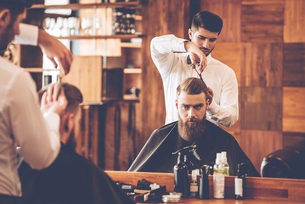 La coupe de cheveux doit être parfaite. jeune homme barbu se coupe les cheveux par le coiffeur alors qu'il était assis sur une chaise au salon de coiffure devant le miroir