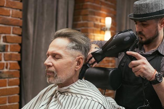 Coupe de cheveux de grand-père chez le coiffeur dans le salon de coiffure
