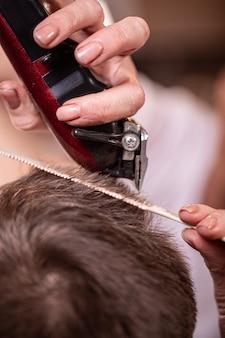 Coupe de cheveux gros plan. mains tenant une tondeuse à cheveux.