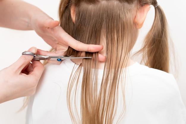 Coupe de cheveux en gros plan. maman fait une coiffure pour sa fille à la maison toute seule. ciseaux professionnels. économiser de l'argent dans un salon de beauté.