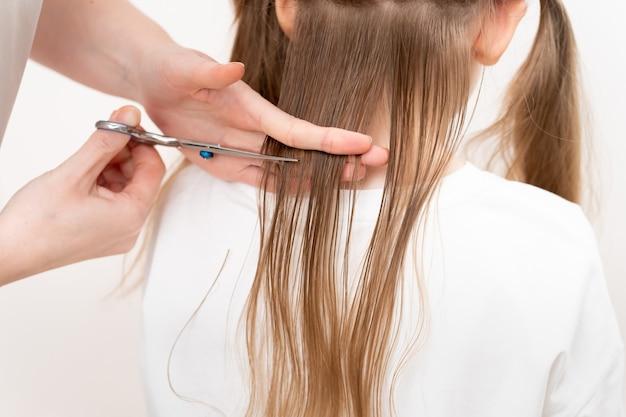 Coupe de cheveux en gros plan. maman fait une coiffure pour sa fille à la maison toute seule.