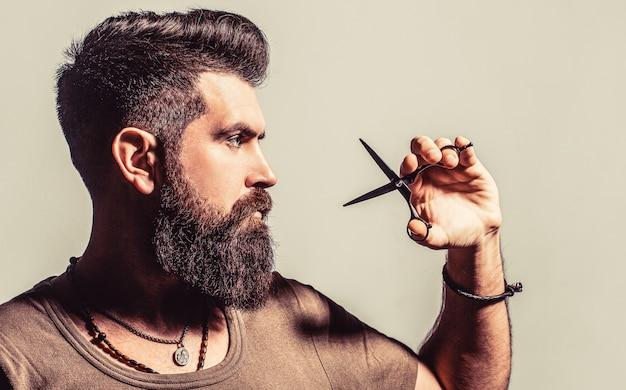 Coupe de cheveux de l'homme dans les ciseaux de coiffeur de coiffeur salon de coiffure ciseaux de coiffeur salon de coiffure vintage rasage