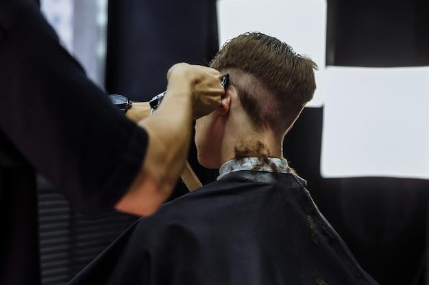 Coupe de cheveux masculine avec rasoir électrique. barber fait la coupe de cheveux pour le client au salon de coiffure en utilisant une tondeuse à cheveux. coiffure homme avec rasoir électrique.