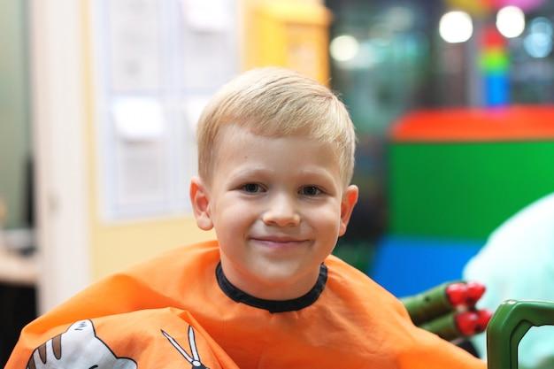 Coupe de cheveux d'un petit garçon dans un salon de coiffure pour enfants