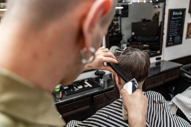 Coupe de cheveux pour hommes. un coiffeur élégant coupe un homme. style homme