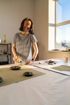 Coupe et couture dans un atelier de couture jeune femme travaillant avec du tissu dans un atelier de design