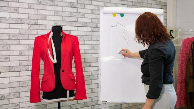 Coupe et couture de vêtements faits à la main. la couturière dessine un motif de veste sur un tableau blanc dans un atelier de couture. le créateur de vêtements crée un nouveau modèle de veste. femme au travail dans une entreprise de couture.