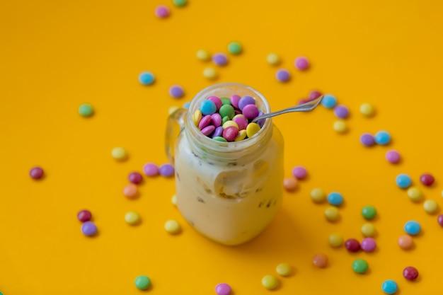 Coupe de crème glacée avec des bonbons à la dragée sur jaune