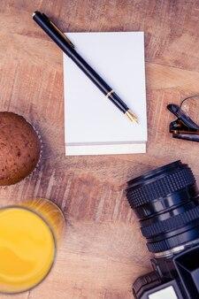 Coupe du gâteau et boisson avec le bloc-notes par la caméra sur la table dans le bureau