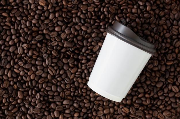 Coupe du papier blanc sur fond de grain de café. vue de dessus