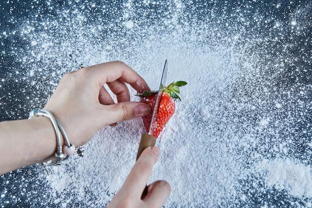 Coupe femme fraise fraîche sur une surface bleue avec un couteau