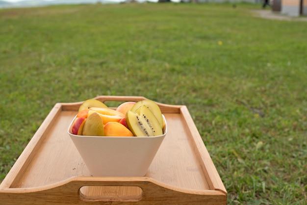Coupe de fruits se dresse sur une table en bois.
