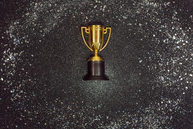 Une coupe gagnante en or avec des étincelles d'argent sur un bureau noir