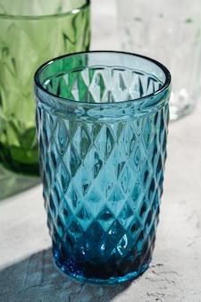 Coupe géométrique en verre bleu près d'un verre à boisson vert et transparent