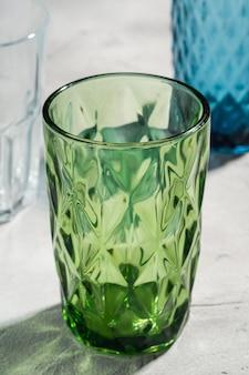 Coupe géométrique en verre vert près de verre à boisson bleu et transparent avec des rayons de lumière d'ombre colorée sur fond de béton de pierre, macro de vue d'angle