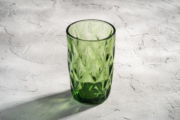 Coupe géométrique en verre vert avec des rayons de lumière d'ombre colorée sur fond de béton de pierre, vue d'angle